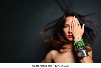 Young brunette with flowing flowing hair covered half her face with her palm. In the hands of many luxurious beautiful bracelets with precious stones