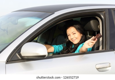 young brunette girl behind the wheel driving displays documents