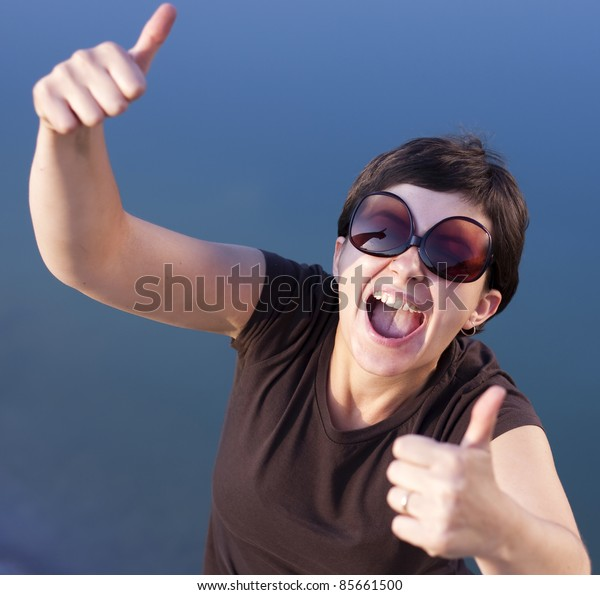 Young brunette girl with big funny sunglasses making thumbs up gesture  - shallow depth of field