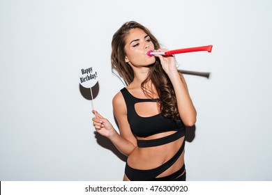 Young brunette girl in bikini sitting and blowing in whistle over white background