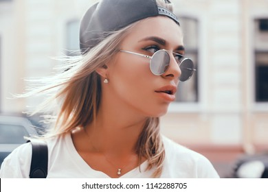 Young brunette girl in black standing outside and watching the sunset in the city, the sun shines brightly, fashionable clothes on a girl, hipster style,, tattoo, street photo, mood, freedom
