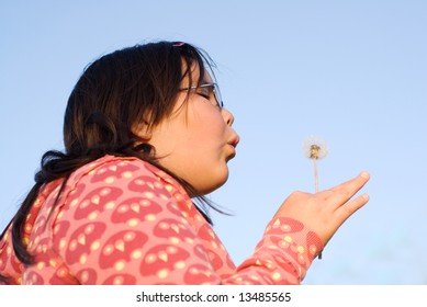 A young brunette girl blowing on some dandelion seeds making a wish