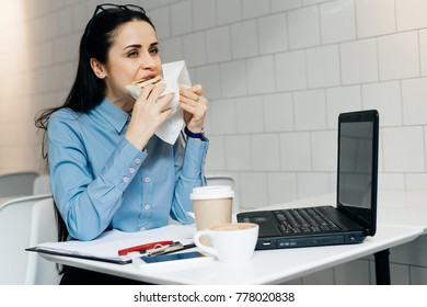 young brunette girl in a blue shirt eating a sandwich in a cafe, on the desk is a laptop for work
