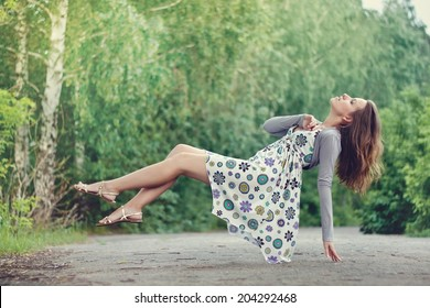 Young brunette girl in colorful dress levitating in the park. Green trees lit with bright summer sunlight.