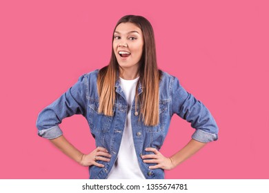 a young brunette girl in a denim jacket smiles mischievously on a pink background