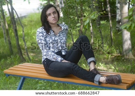 Young brunette girl in fashionable jeans, a light shirt, in brown shoes,  sits 88f1b6d321