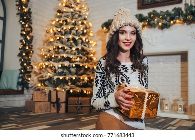 Young brunette girl with gift box near Christmas tree and decorated fireplase in cozy home interior