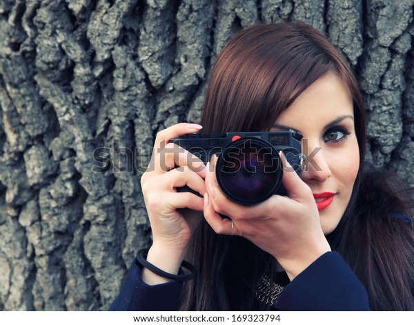 Young brunette girl holding a classic camera