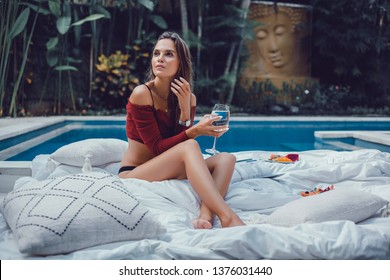 young brunette girl with makeup long legs poses in blue swimsuit in a pool of blue water, luxury Villa with sea views, palm trees, luxury,VIP area,beautiful tan body,tanned skin,smartphone, Bali,wine