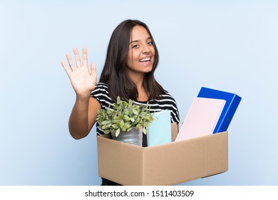 Young brunette girl making a move while picking up a box full of things saluting with hand with happy expression