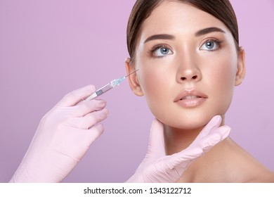Young brunette girl with naked shoulders wearing evening nude up with long lashes posing at pink studio background, hands in medical glove on patient's face, doing injections.