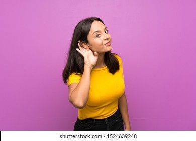 Young brunette girl over isolated background listening to something by putting hand on the ear