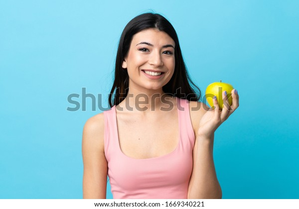 Young brunette girl over isolated blue background with an apple