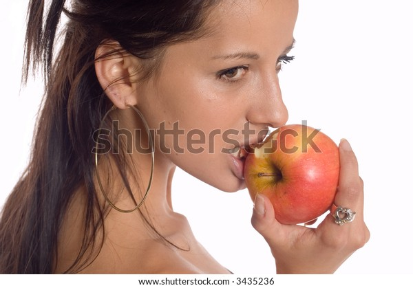 Young brunette girl posing and eating a apple
