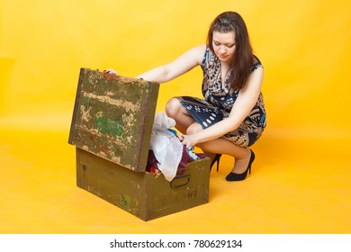 young brunette girl puts away things in a wooden box, on yellow background