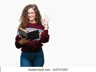 Young brunette girl reading a book wearing glasses over isolated background doing ok sign with fingers, excellent symbol