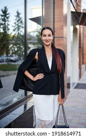 Young brunette girl with red pony tail, wearing stylish black jacket and white silk dress, standing in front of modern glass building. Pretty business woman on lunch break. Female portrait in city.
