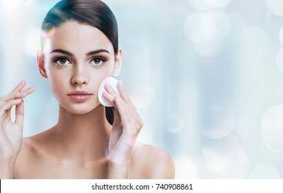 Young brunette girl removing makeup from her face. Photo of beautiful girl with cotton pads  on shiny silver background. Skin care and beauty concept.