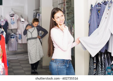 Young brunette girl shopping comfortable sleepwear for man in store