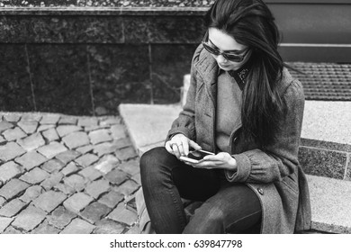 Young brunette girl sitting on the street with cellphone, black and white