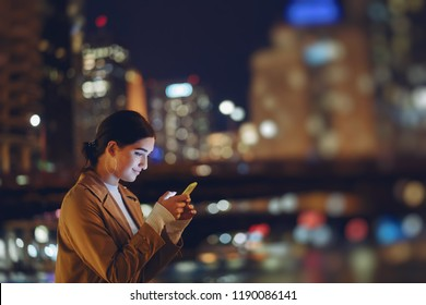 young brunette girl standing at night by Chicago skyline