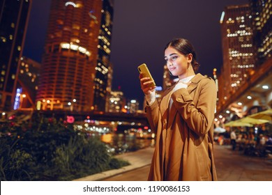 young brunette girl standing at night with phone by Chicago skyline