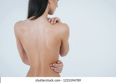 Young brunette girl turn her back to the camera while staying naked on the white background.