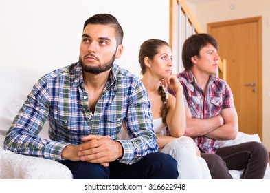 Young brunette girl and two men at home: problems of love triangle. Selective focus