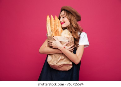 Young brunette happy lady in hat hug pack with baguettes and enjoy them isolated over pink