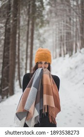 young brunette is hiding behind colorful scarf and smiles slightly and looks magically. Portrait of blue-eyed girl in snowy landscape and during snowfall. Contrast white and black. Set Sail champagne.