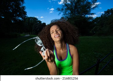 Young Brunette Hispanic woman wearing broken glasses and making silly faces in Central Park, NYC