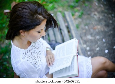 Young brunette intellectual woman wearing a white lace dress while reading a book on a wooden bench in the park, in a warm day of summer, high-angle