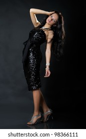Young brunette lady in black dress posing