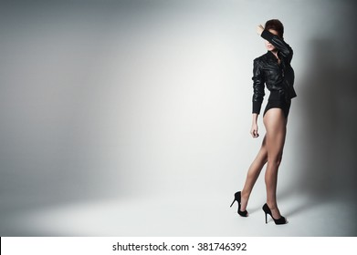 Young brunette lady in black jacket posing on grey background