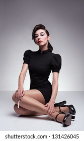young brunette lady holding a cigarette and wearing a black  retro dress sitting on floor and posing on grey background
