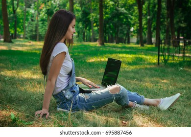young brunette with long hair sitting on a green grass with laptop