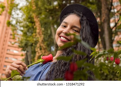 A young brunette in love burns with passion while holding a beautiful red rose. She shows off her wide smile in conjunction with her blue dress and her fedora hat.