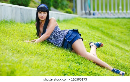 young brunette lying on the grass in the park