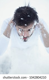 Young brunette man dressed in t-shirt starting cold winter morning with washing face with pure white snow to promote health, sitting on knees at ground. Fresh and vitalize treatment for strong male.
