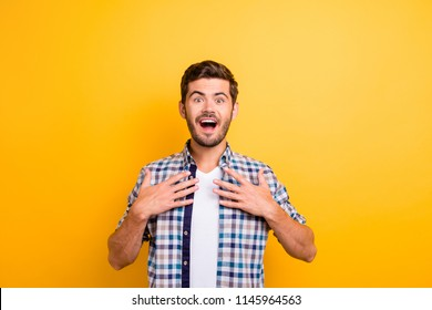 I won?! Young brunette man with an enthusiastic face look into the camera put his hands on his chest and wide open mouth and eyes with surprise isolated on shine yellow background