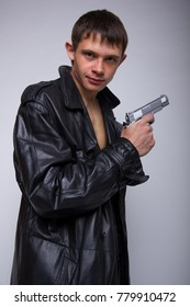 young brunette man in a long leather coat. emotional portrait. clothes on the naked body. the image of a gangster with a gun. problematic skin: acne and black spots. Wallpaper for desktop