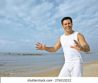 young brunette man on beach at sea smiling,  in white dress big muscles