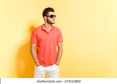 Young brunette man in sunglasses with stubble posing looking away hands in the pocket standing against yellow background.