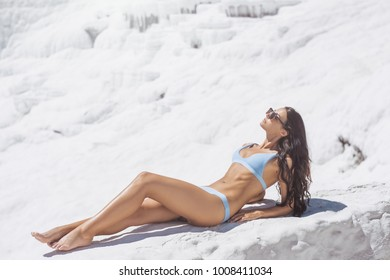 Young brunette mixed race Asian Caucasian woman model with perfect tan sunbathing in swimsuit on Pamukkale Cotton Castle Travertine pools and terraces where people love to visit in Turkey.