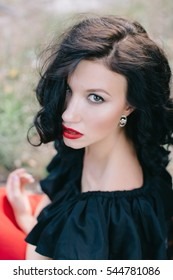 Young brunette model in black jacket and red lips posing in the woods near the tree