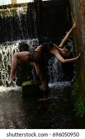 Young brunette model posing against a waterfall