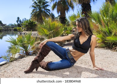 Young brunette model posing in large boots on a tropical beach location