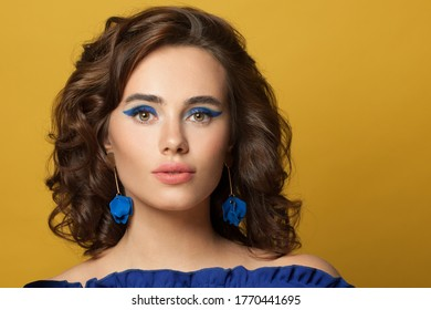 Young brunette model woman with curly bob haistyle and blue earrings on vivid yellow background