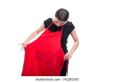 Young brunette seller putting red apron on and wearing it at her job isolated on white