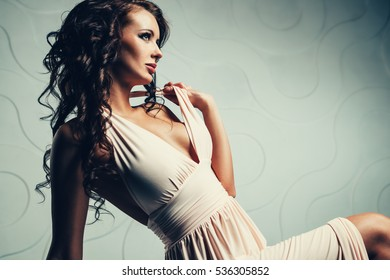 Young brunette sexy slim woman in white dress looking aside portrait
